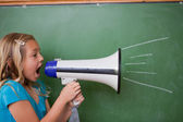 Young schoolgirl screaming through a megaphone — Stock Photo