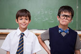 Schoolboys posing in front of a chalkboard — ストック写真