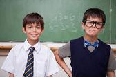 Skolpojkar poserar framför svarta tavlan — Stockfoto
