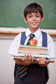 Portrait of a schoolboy holding books and an apple — Stock Photo