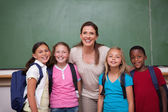 Schoolteacher posing with her pupils — Stock Photo