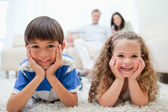Happy kids lying on the carpet with parents behind them — Stock Photo