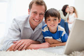 Smiling son and dad using laptop on the carpet — Stock Photo