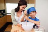 Mother and son having fun preparing a cake — Stock Photo