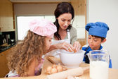 Mother making cookies with her kids — Stock Photo