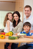 Young family standing in the kitchen — Stock Photo
