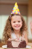 Slice of cake in front of girl — Stock Photo