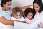 Parents reading a story for their children — Stock Photo