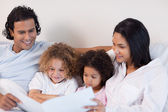 Happy family enjoys reading a story together — Stock Photo