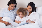 Happy family enjoys reading a book together — Stock Photo
