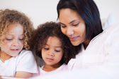 Woman sitting on the bed with her daughters — Stock Photo