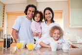 Happy family standing in the kitchen together — Stock Photo