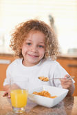 Happy girl eating cereals for breakfast — Stock Photo
