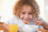 Smiling girl having breakfast — Stock Photo