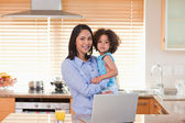Mother and daughter with notebook in the kitchen together — Stock Photo