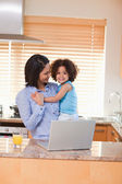 Mother and daughter with notebook in the kitchen — Stock Photo