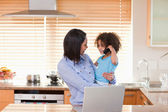 Mother and daughter using notebook and cellphone in the kitchen — Stock Photo