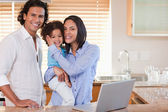 Family surfing the internet in the kitchen together — Stock Photo