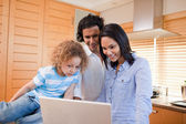 Happy family surfing the internet in the kitchen together — Stock Photo