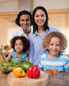 Family with salad together in the kitchen — Stock Photo