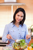 Woman stirring salad in the kitchen — Stock Photo
