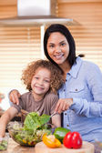 Mother and daughter preparing salad in the kitchen together — Stock Photo