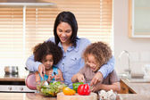 Mother and daughters preparing salad in the kitchen together — Stock Photo