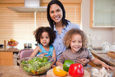Mother and her daughters preparing salad in the kitchen together — Stock Photo