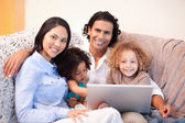 Family using laptop on the sofa together — Stock Photo