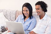 Couple with laptop on the couch — Stock Photo
