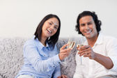 Couple celebrating with sparkling wine on the couch — Stock Photo