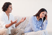 Man on the sofa trying to apologize to his girlfriend — Stock Photo