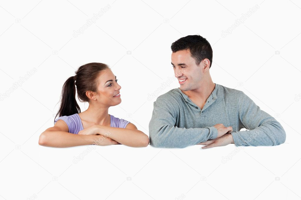 Young couple looking at each other while leaning on a wall against a white background  Stock Photo #11200041