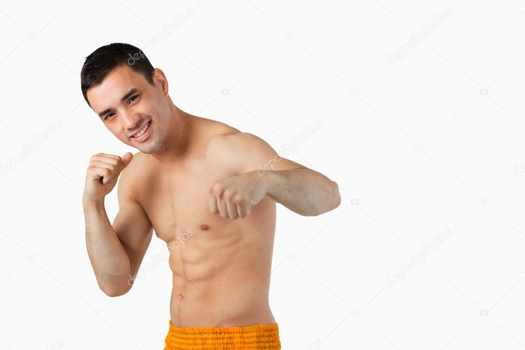Young martial arts fighter doing left hook against a white background — Stock Photo #11200456