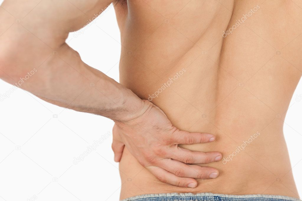 Young man experiencing back pain against a white background — Stock Photo #11200773