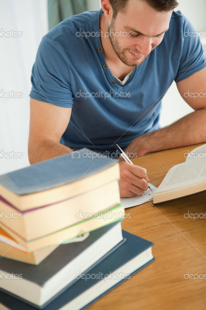 Smiling male student preparing book report  Stock Photo #11201829