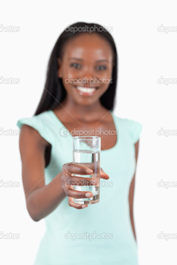 Refreshing glass of water offered by young woman against a white background — Stock Photo #11202045