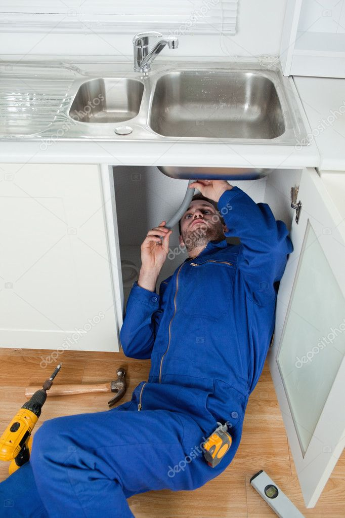 Portrait of a smiling plumber fixing a sink in a kitchen — Stock Photo #11204006