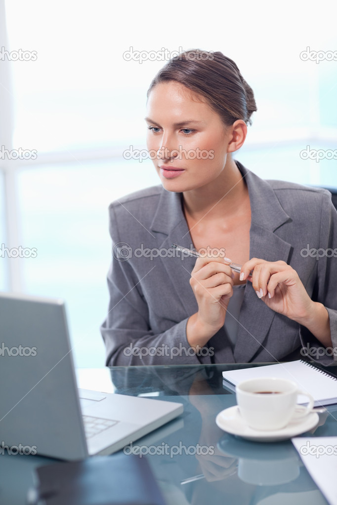 Portrait of a doubtful businesswoman taking notes in her office — Stock Photo #11204668
