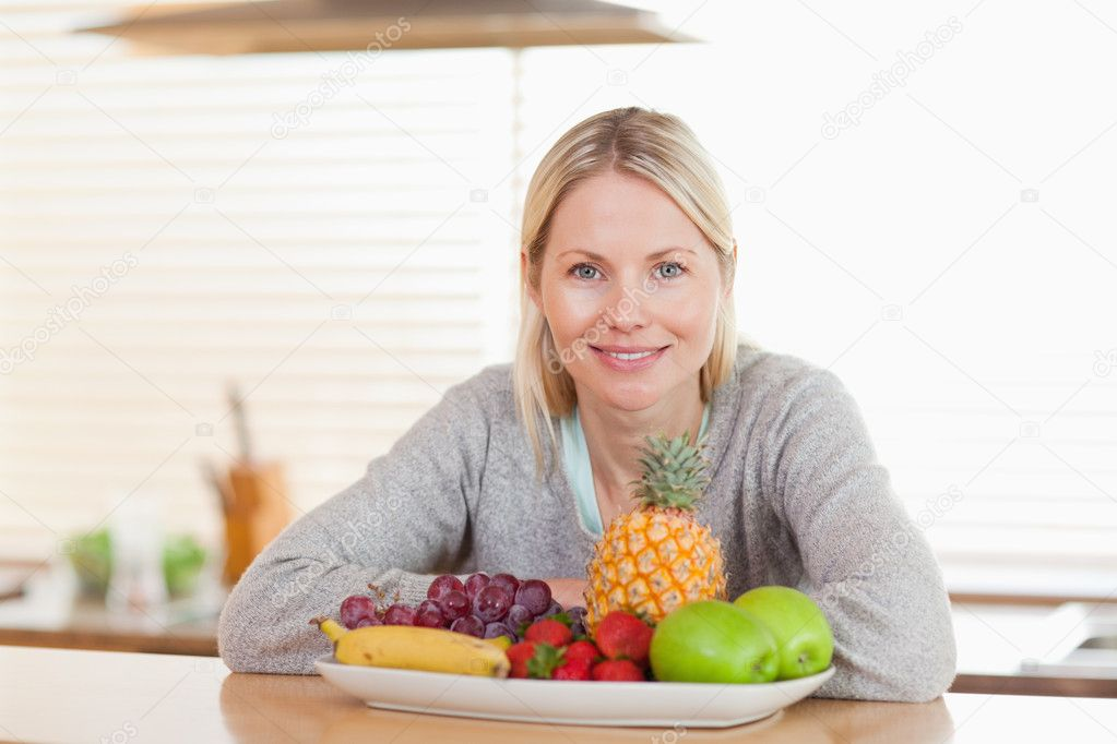 Young woman sitting in the kitchen with a plate of fruits — Stock Photo #11205670