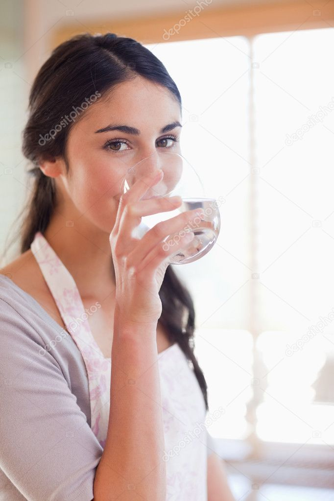 Portrait of a beautiful woman drinking water in her kitchen — Stock Photo #11206657