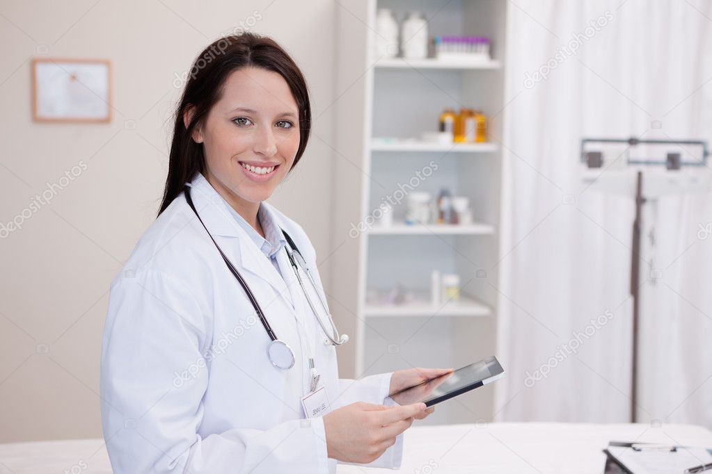 Smiling doctor using a tablet computer in a hospital — Stockfoto #11207335