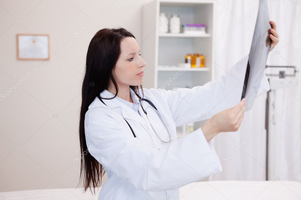 Young doctor looking at a set of X-ray in a hospital — Stock Photo #11207339