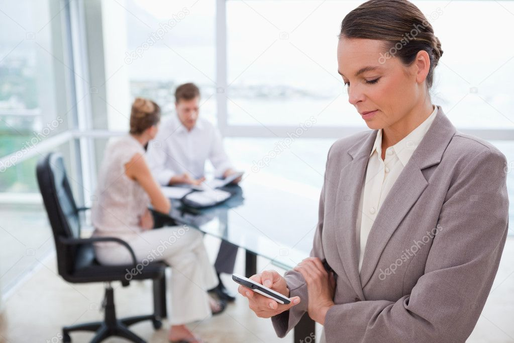 Standing real estate agent with cellphone and sitting clients behind her — Stock Photo #11208430