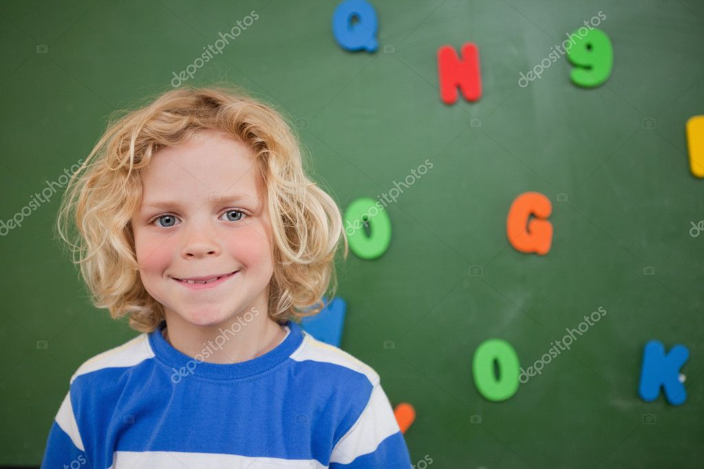 Schoolboy posing in front of a blackboard in a classroom — Stock Photo #11208664