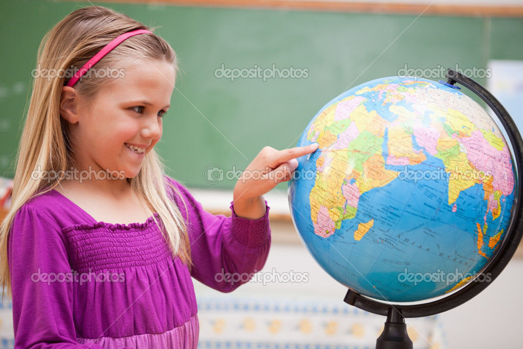 Cute schoolgirl pointing at a country on a globe — Stock Photo #11208712