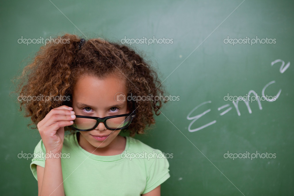 Schoolgirl looking above her glasses in front of a blackboard — Stock Photo #11209393