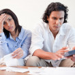 Frustrated couple doing their calculations in the living room - Stock Photo