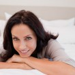 Smiling woman on the bed — Stock Photo