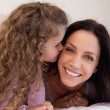 Little daughter giving her mother a kiss — Stock Photo